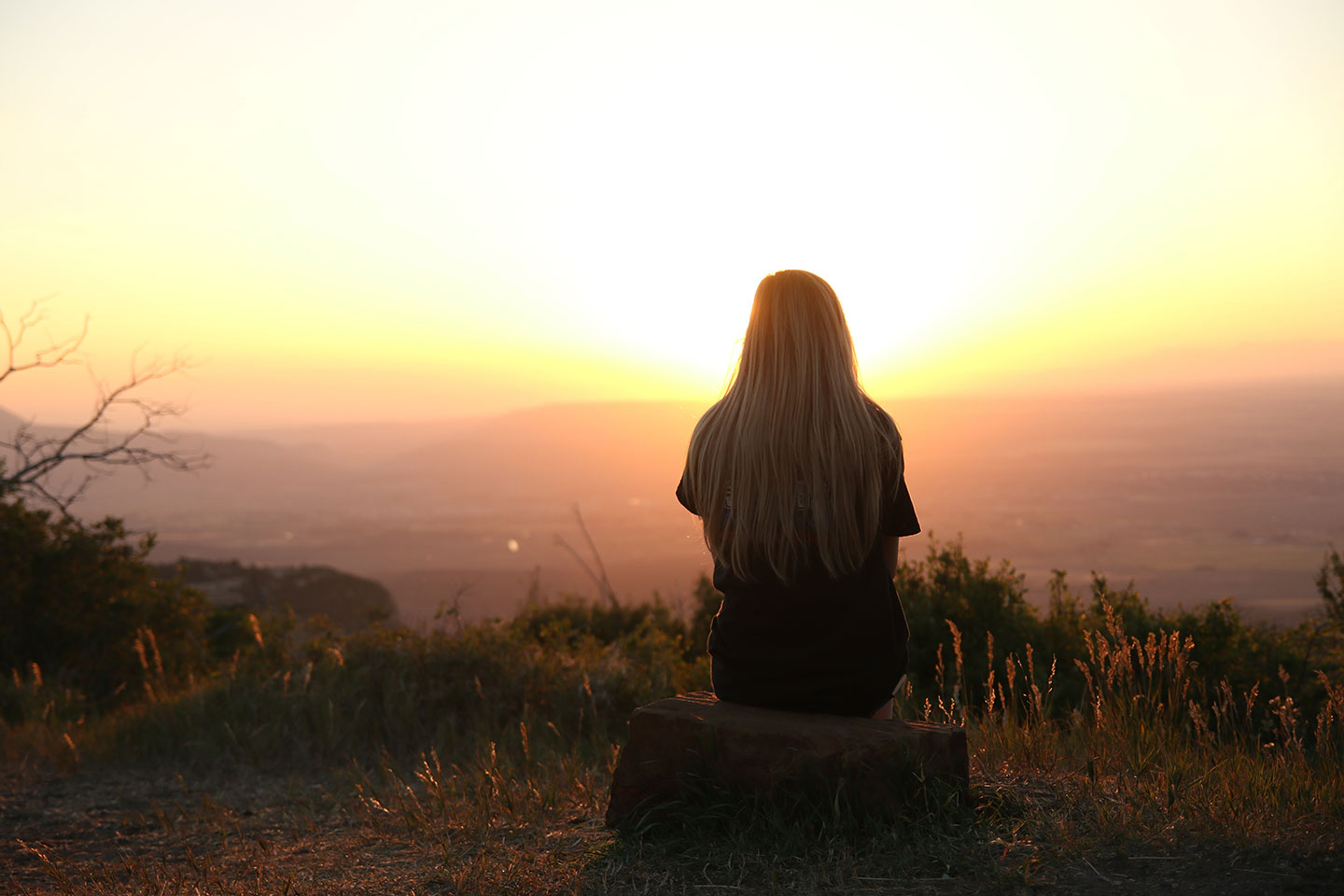 Woman overlooking a valley at sunset
