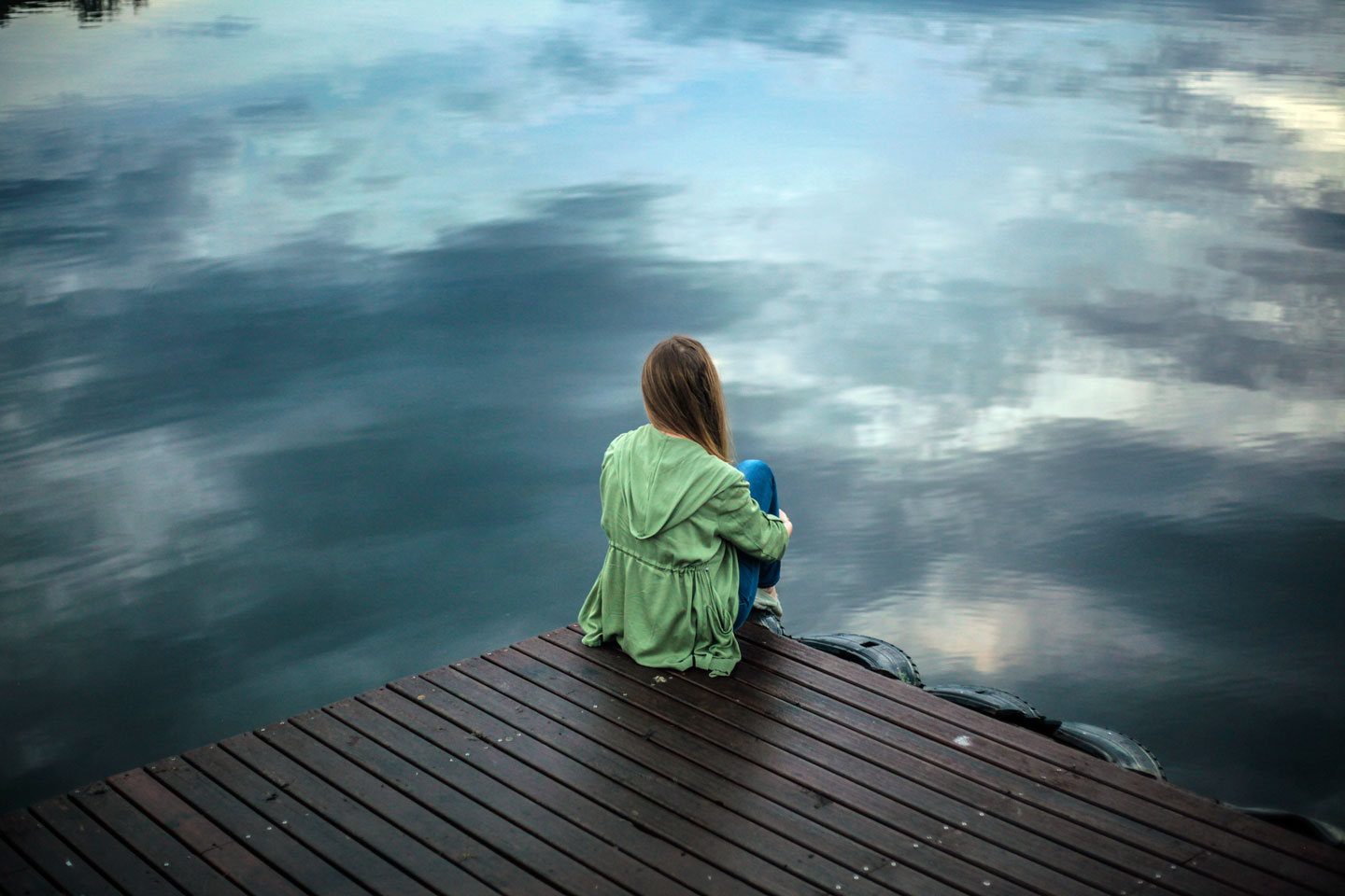 Woman sitting on a wooden dock overlooking the lake