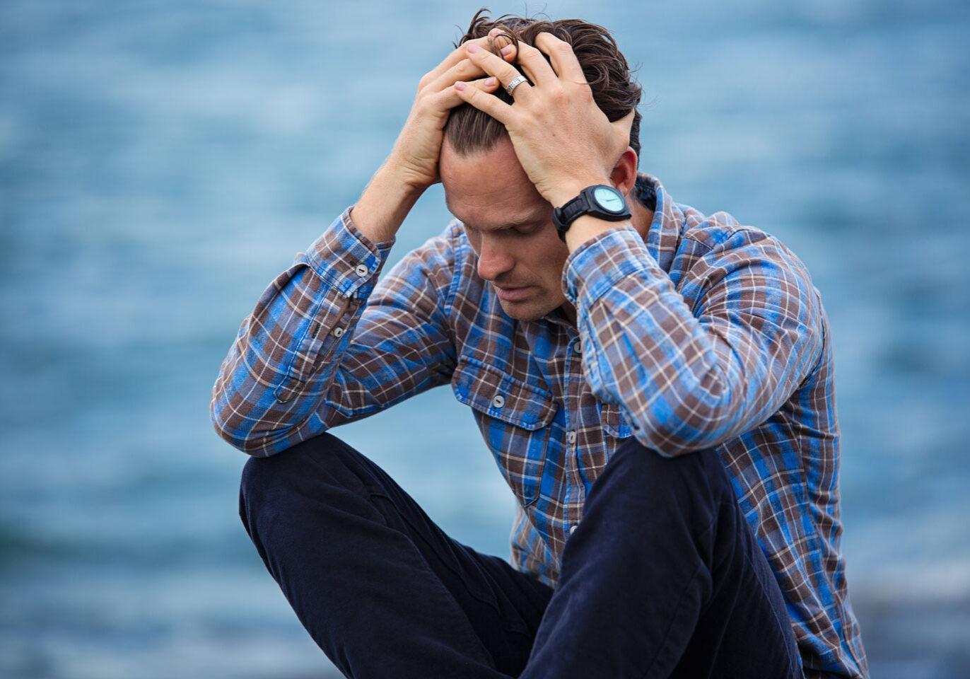 Man upset on dock overlooking a lake